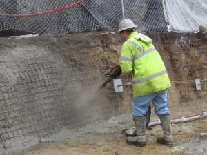 Image of shotcrete being applied over the installed helical tieback anchors within the retaining wall